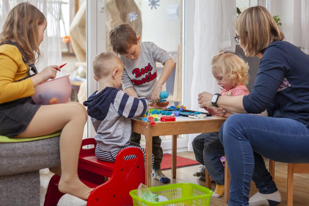 Frau und vier Kinder basteln auf einem Tisch mit Knetmasse