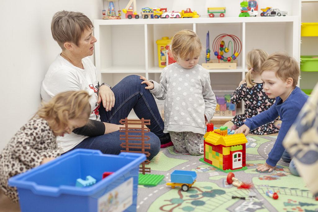 Frau und vier Kleinkinder spielen mit Bauklötzen