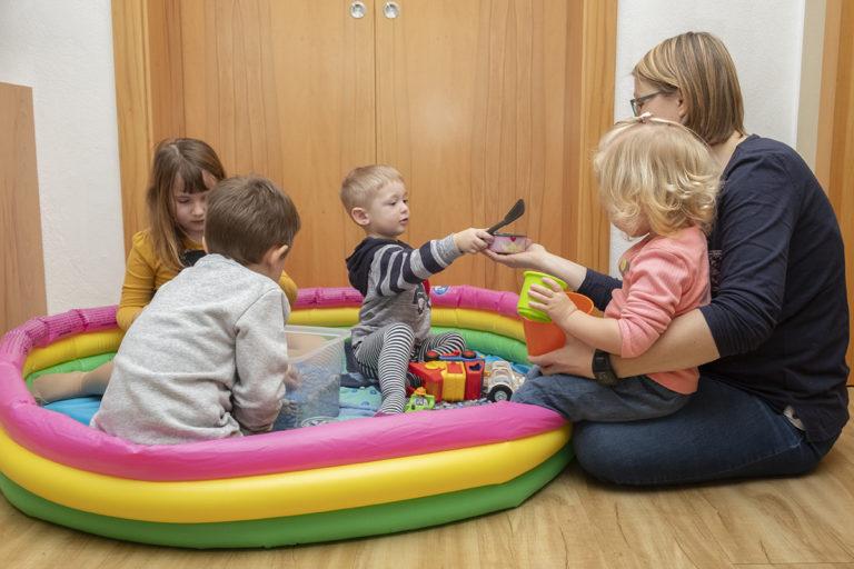 Frau und vier Kinder spielen und ein Kleinkind reicht ihr ein Spielzeug