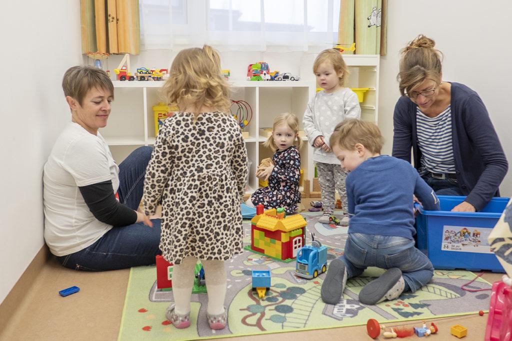 Zwei Frauen und vier Kleinkinder spielen zusammen mit Bauklötzen