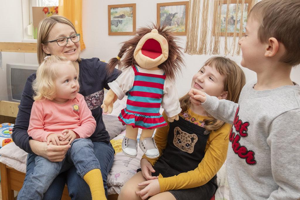Frau mit Handpuppe und drei Kinder