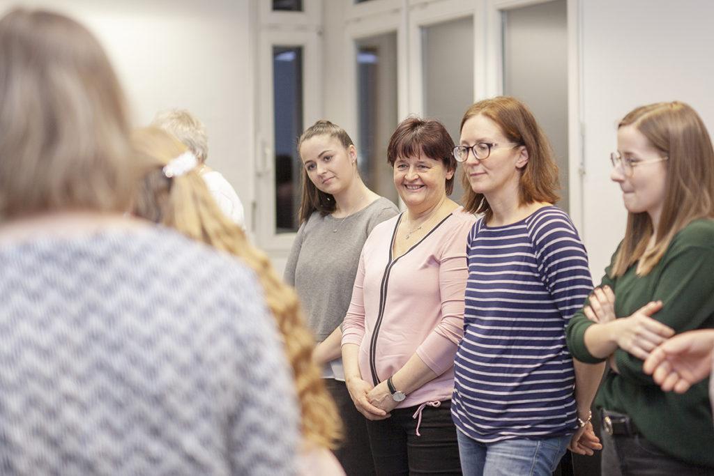 Vier Frauen in einer Kursgruppe hören der Vortragenden zu