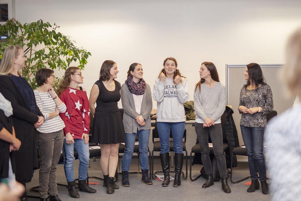 Kursgruppe im halben Sesselkreis, alle hören einer Frau zu