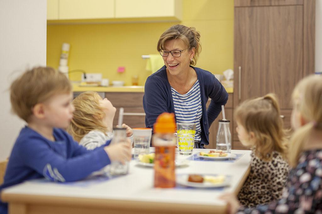 Frau und vier Kleinkinder sitzen an einem Tisch und essen