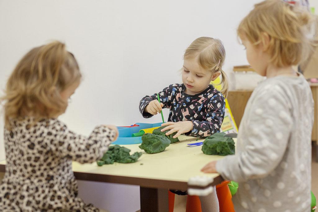 Drei Kleinkinder basteln auf einem Tisch mit Knetmasse
