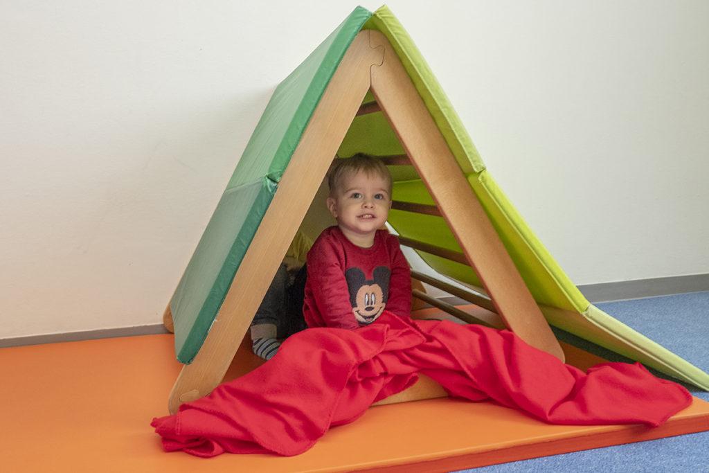 Bub unter selbstgebautem Zelt aus Turnmatten
