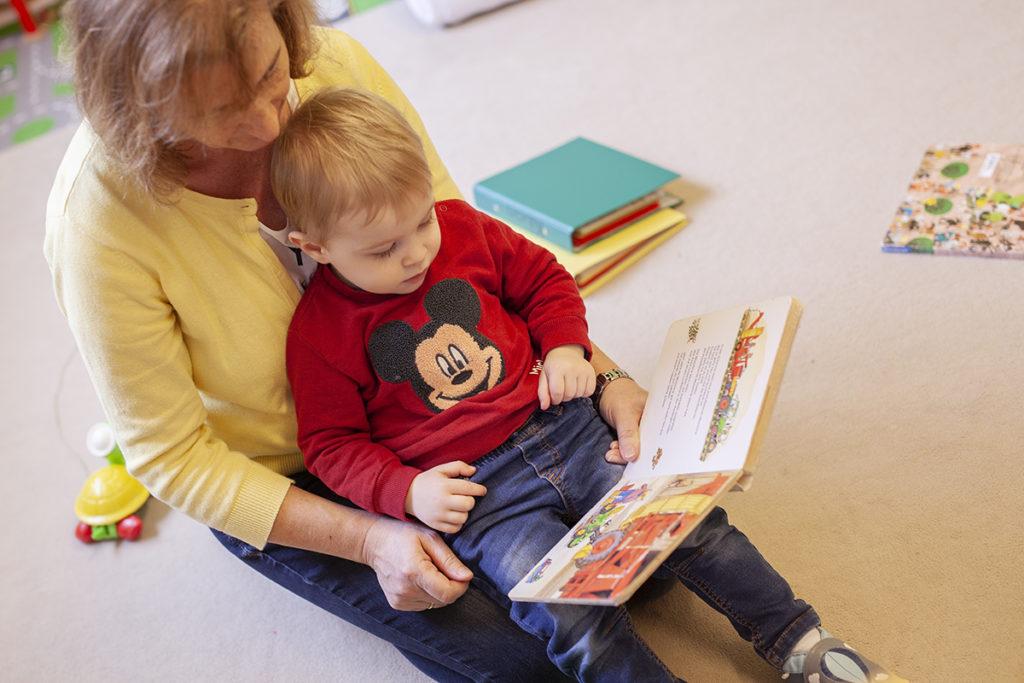Kleinkind sitzt auf dem Schoß einer Frau und beide schauen sich ein Bilderbuch an
