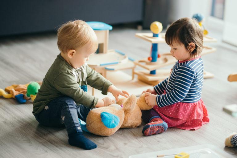 Zwei Kleinkinder spielen mit einem Teddy
