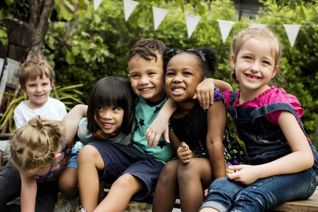 Gruppe von sechs Kindern sitzen nebeneinander, halten sich in den Armen und lächeln