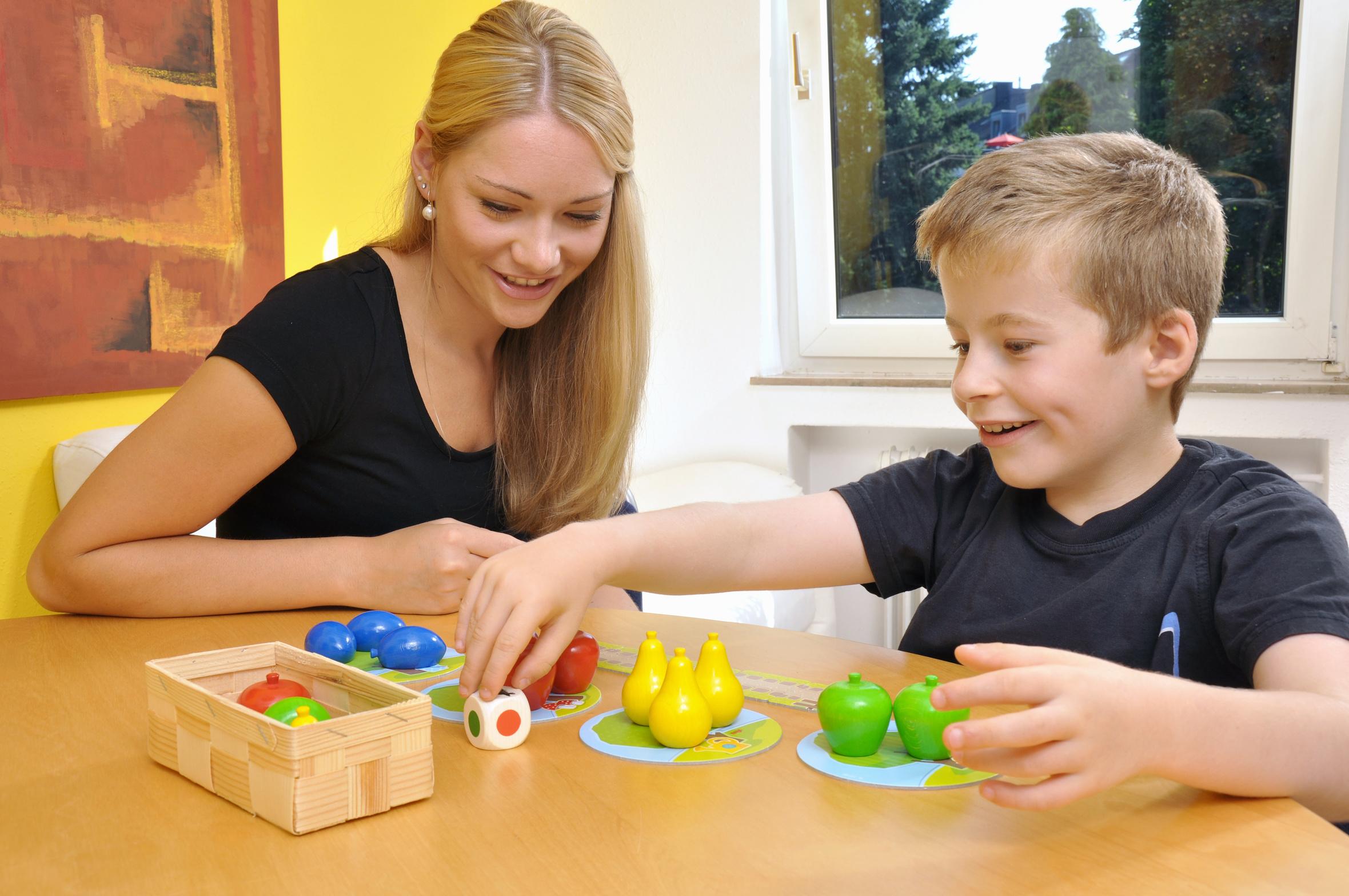 Frau und Junge spielen ein Gesellschaftsspiel