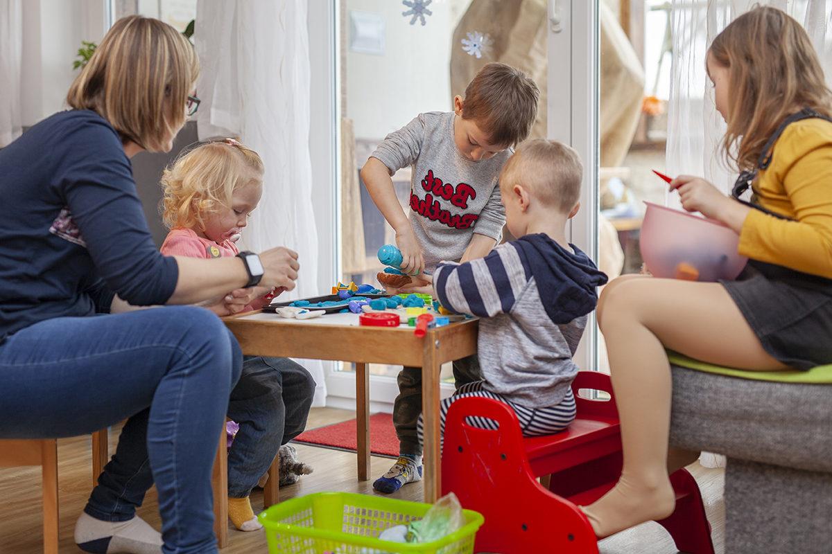 Die Tagesmutter zu Hause begleitet die spielenden Kinder.
