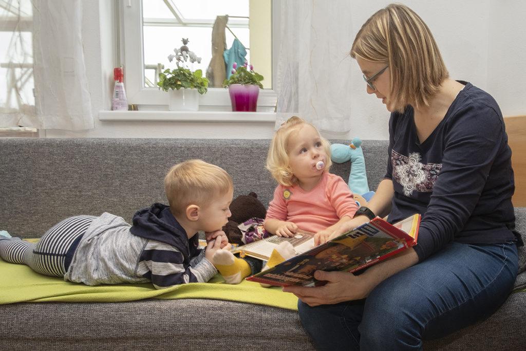 Die Tagesmutter geht auf die individuellen Bedürnisse der Kinder ein. Sie liest zwei kleinen Tageskindern eine Geschichte vor und beantwortet ihre Fragen.