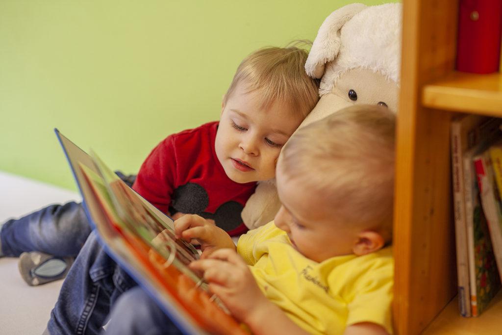 Zwei Kleinkinder schauen sich ein Buch gemeinsam an, während sie im Kindernest liebevoll von der Tagesmutter betreut werden.