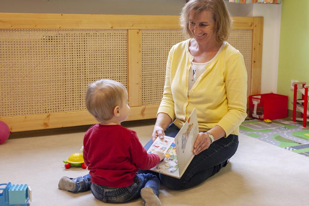 Die Tagesmutter schaut mit dem Kleinkind ein Bilderbuch an.