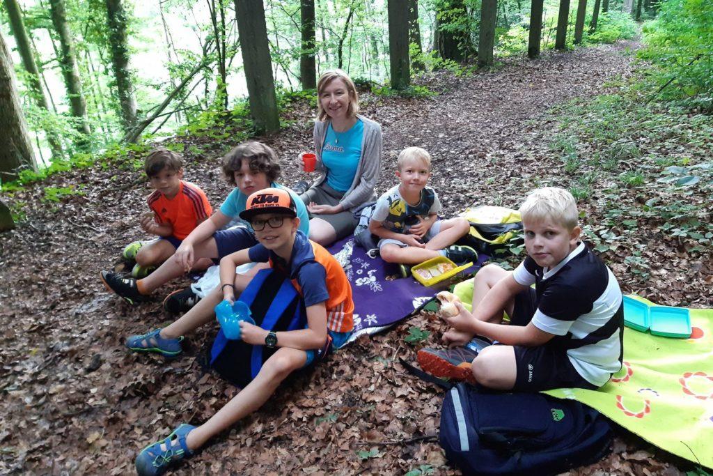 Die Kinder sitzen mit der Tagesmutter im Wald und machen ein Picknick - ein Programmpunkt der Ferienbetreuung mit den Tagesmüttern.